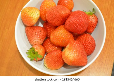 The red starwberries in the white bowl