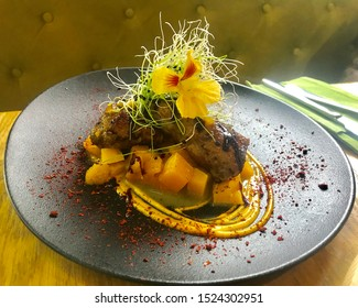 red steak meat on grill made of mango composition made on grey dish wonderful decorated with flower on creative concept food shoot macro restaurant bistro buy.