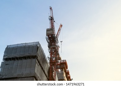 red steel truss tower crane stick with high rise building construction with net protection with steel scaffolding frame help progress of its work by hoisting heavy material and run metal formwork