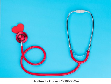 Red stethoscope or phonendoscope  on blue table background with copy space for  text. Medicine concept
