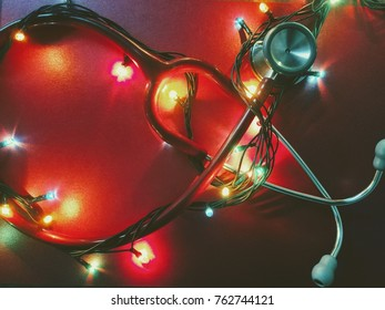 Red stethoscope and shining colorful Christmas lights isolated on red background, vintage toned. Medical holidays or Christmas in hospital concept