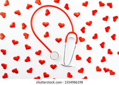 Red stethoscope surrounded by hearts seen from above isolated on white background, coronary heart disease concept.