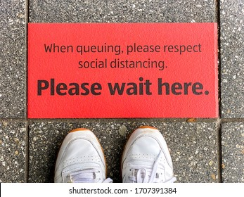 """Red sticker on floor outside a supermarket with """"Please wait here"""" message as part of social distancing measures imposed to control the outbreak of coronavirus in the UK"""