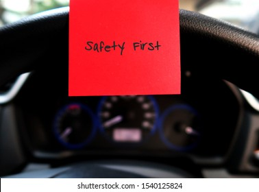 Red sticky note with text written SAFETY FIRST , on the car steering wheel , to remind driver to drive carefully and with awareness