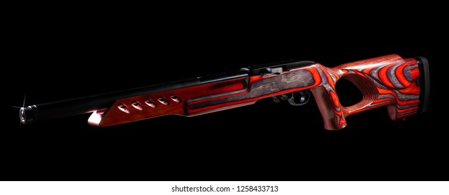 Red stocked rifle with a thumbhole on a black background