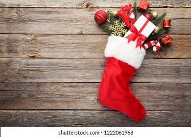 Red stocking with fir-tree branches and christmas decorations on wooden table