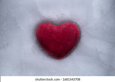 Red stone heart frozen in ice with a cracks, a symbol of love or betrayal or separation.