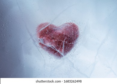 Red stone heart frozen in ice with a big cracks, a symbol of love or betrayal or separation.