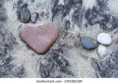 red stone heart, sea stone in the shape of a heart on the sand