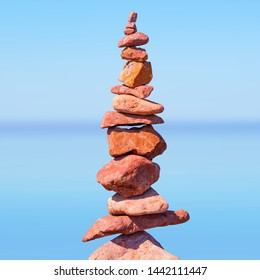 Red stones stack tower construction - unstable balance and horizontal blurred light blue sea surface, isolated objects. Symbol of ambition or succesful business project. For book or brochure cover.