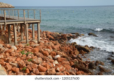 Red stones washed by sea water on a wooden pier