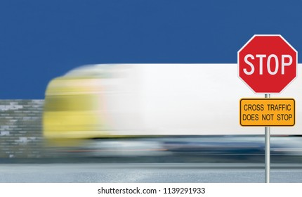Red stop road sign, motion blurred truck vehicle traffic background. Give way regulatory warning octagon white frame. Yellow cross traffic does not stop text signage metallic pole post blue summer sky