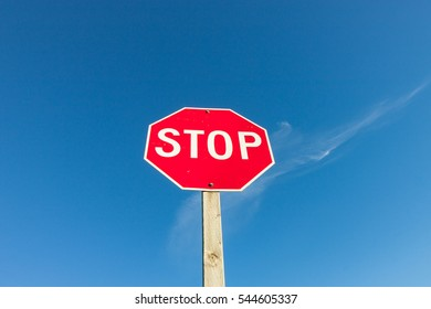 Red Stop Sign Against Blue Sky