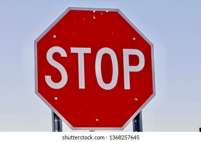 A red stop sign appears before a blue sky.
