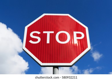 Red Stop Sign with Blue Sky and Clouds Background.