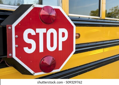 A red stop sign with lights on the side of a yellow school bus.