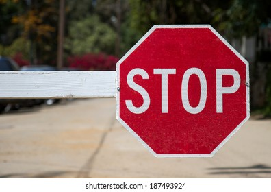 Red stop sign mounted on a gated entry arm.