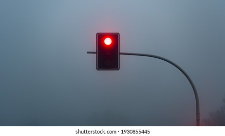 Red stop traffic light lamp during heavy fog outside the city. Mystery atmosphere. Road to nowhere.