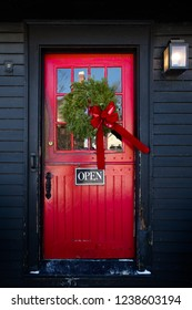 Red Store entrance door with open sign and Christmas wreath