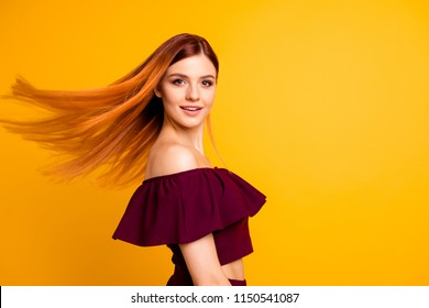 Red straight-haired attractive cute nice cheerful young girl, half turned, wind blowing hair. Isolated over bright vivid yellow background