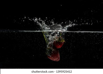 """Red strawberries """"Fragaria ananassa"""" fall into the water. Water splash, drops. Slow motion, black background."""