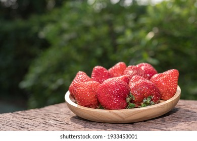 Red strawberries with leaves on bamboo basket, Red strawberry in Bamboo basket on wooden table.