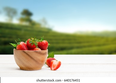 Red strawberries with leaves in a wooden bowl on the wooden table and the plantations background