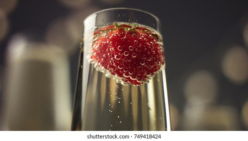 Red strawberry floating in bubbles in a glass of sparkling wine on gray background