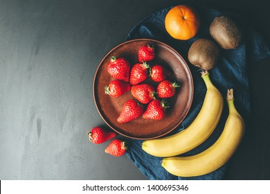 Red strawberry in the plate, banana, orange and kiwi fruit on dark background with blue napkin, top view.