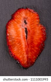 Red strawberry slice on the black background, close up, top view. Cut red strawberry as same as female sexual organ