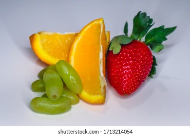 red strawberry slice of oranges and grapes with whit background