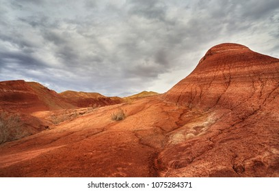 Red striped mountains at overcast sky in desert park Altyn Emel in Kazakhstan