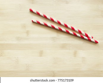 Red striped paper straw for beverage isolated on wooden background. Copy sapce.