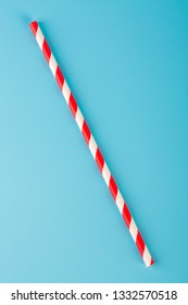 Red striped paper straws on blue background