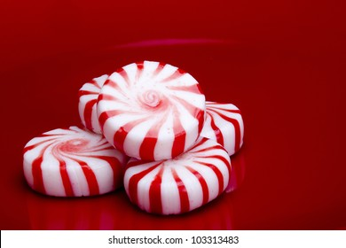 Red striped peppermints on a red background.