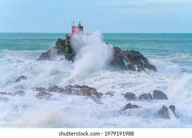 Red structure of beacon on North Rock shrouded in sea and spray ar base of Mount Maunganui with wild dramatic stormy sea crashing around and over it