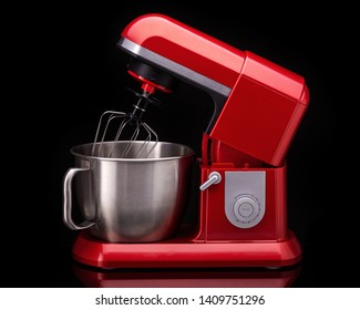 Red stylish mixer for cooking. On a black background.