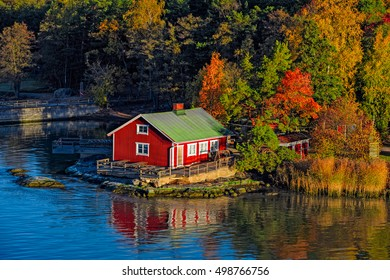 Red summer cabin or mokki in fall color forest on rocky shore of Baltic Sea. Ruissalo island, Turku archipelago, Finland