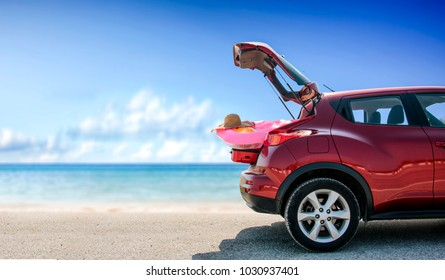 Red summer car on beach with few suitcase and free space for your decoration.