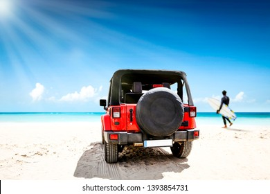 Red summer car on beach. Landscape of ocean and blue sea with sunny day. Surfer on beach with board. Free space for your decoration.