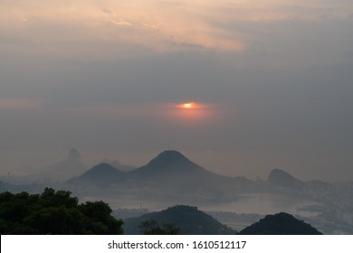 A red sun peaks through a gap in the clouds during a moody grey sunrise from Vista Chinesa in the Tijuca Forest of Rio de Janeiro. There is Sugarloaf Mountain, Lagoa Rodrigo de Freitas and Cabritos.