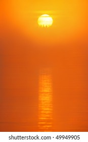 Red sun is rising in the morning mist over water surface