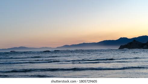 Red sun sets behind crashing waves