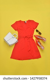 Red sundress and high hell shoes and sunglasses,leather handbag on yellow background