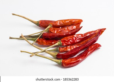 red sun-dried chili pepper with stem isolated on white.