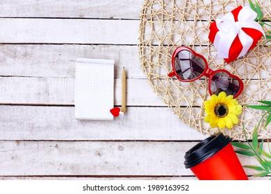 gafas de sol rojas forma de corazón, café, flor amarilla, bloc de notas con lápiz sobre mesa de madera blanca, vista superior, burla hacia arriba