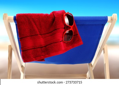 red sunglasses red towel and blue chair closeup on beach
