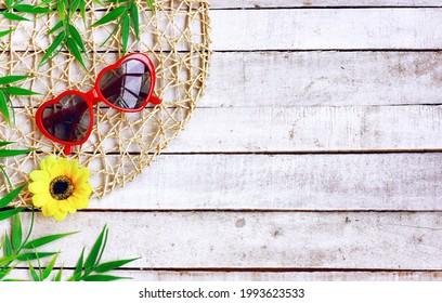 gafas de sol rojas, flor amarilla, hojas verdes sobre una mesa blanca de madera.