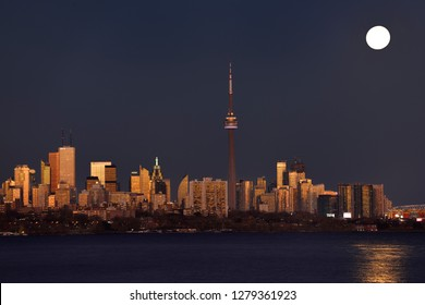 Red sunset glow on Toronto skyline with bright rising supermoon Toronto, Ontario, Canada - November 13, 2016