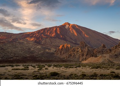Red sunset light at Roques de Garcia rocks and Teide volcano. Tenerife national park, Canary islands, Spain.
